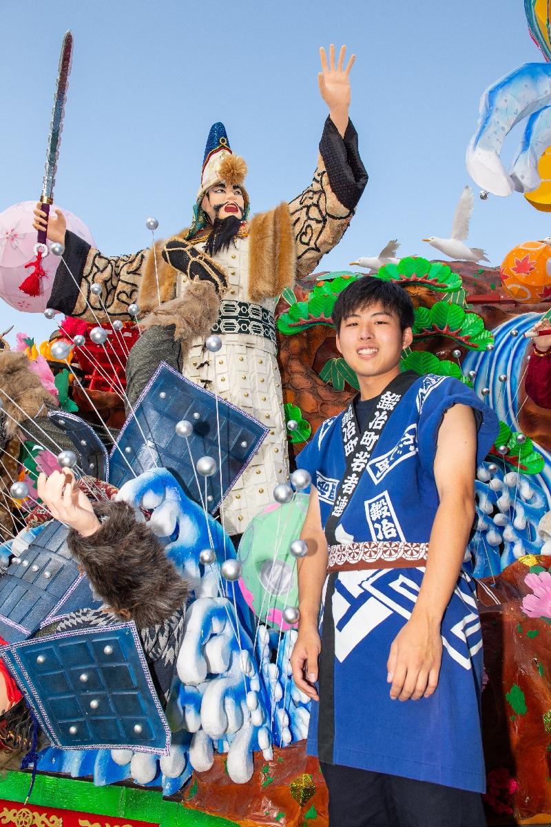 制作した人形の鎧を前に、充実した表情を見せる齋藤伸さん=2日、八戸市の市民広場
