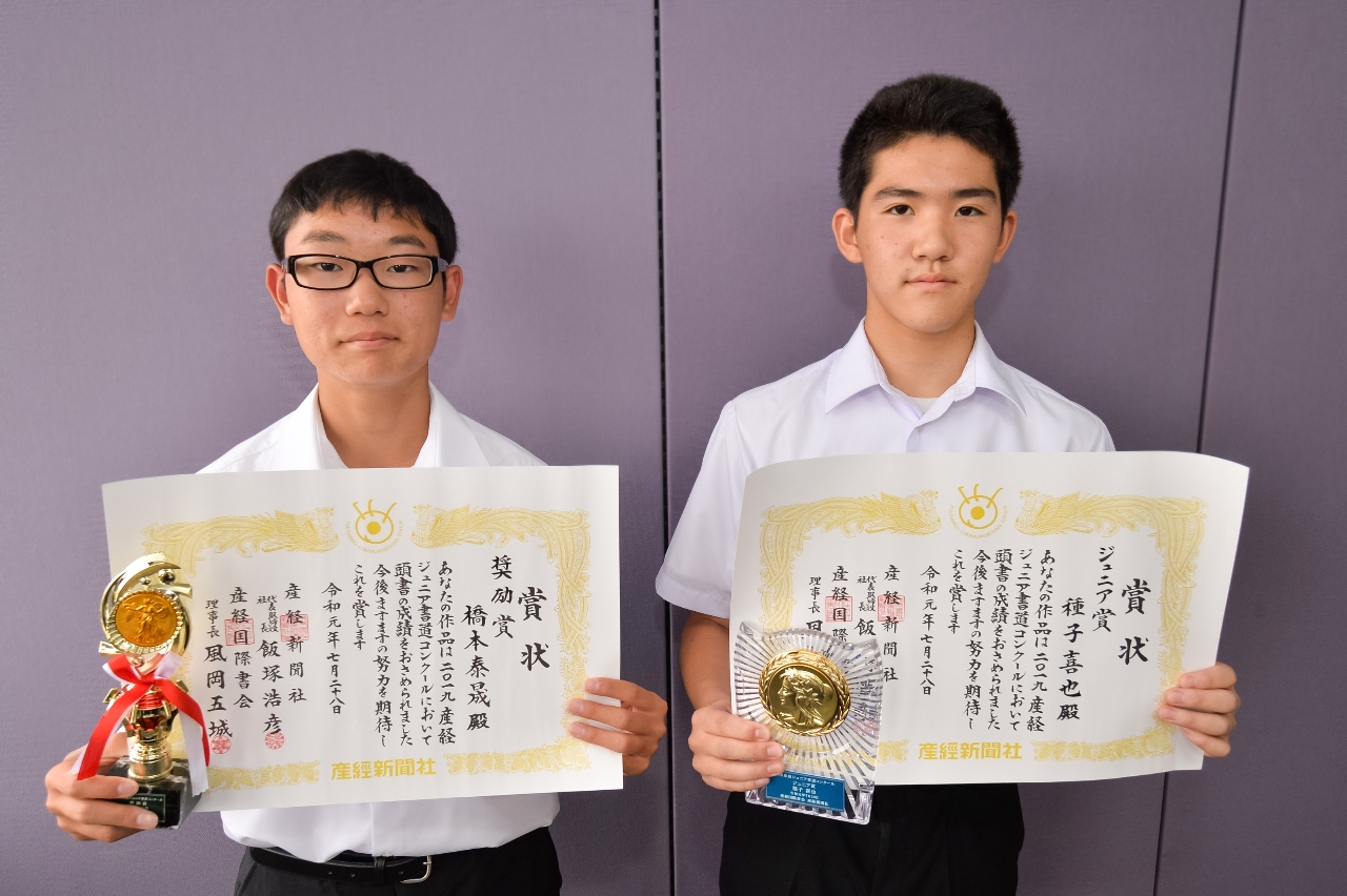 賞状を手に笑顔を見せる種子喜也さん(右)と橋本泰晟さん
