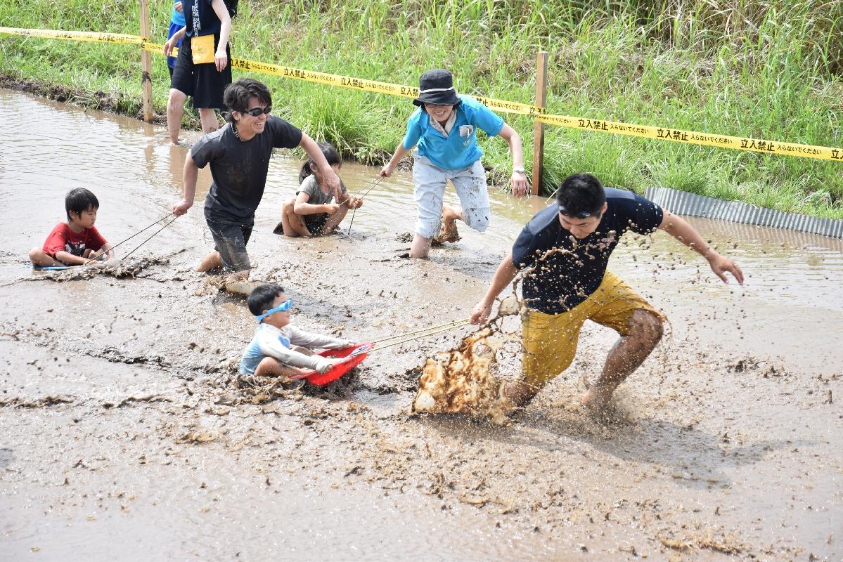泥だらけになりながら速さを競う親子リレー参加者