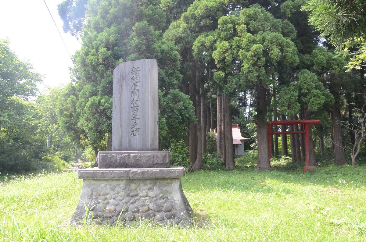 新納屋に残る「新納屋開村百年之碑」。奥には地域を守る神社がひっそりとたたずんでいる=8月上旬、六ケ所村鷹架道ノ下
