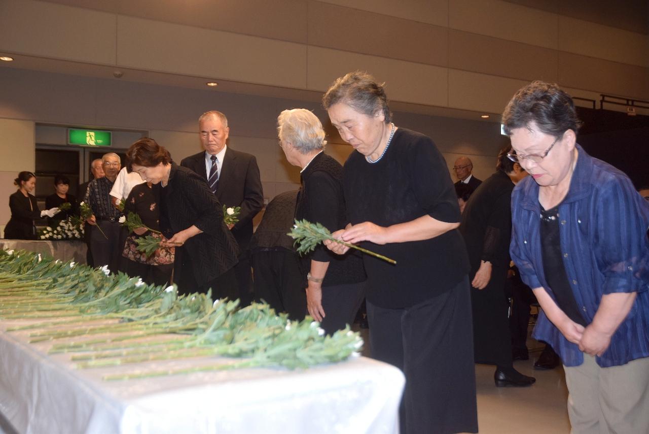恒久平和を誓い献花する参列者