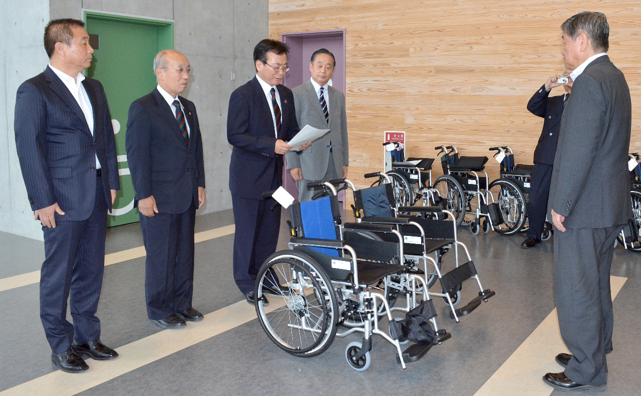 小林眞市長(右)に車いすを贈る中山晃伸会長(左から3人目)