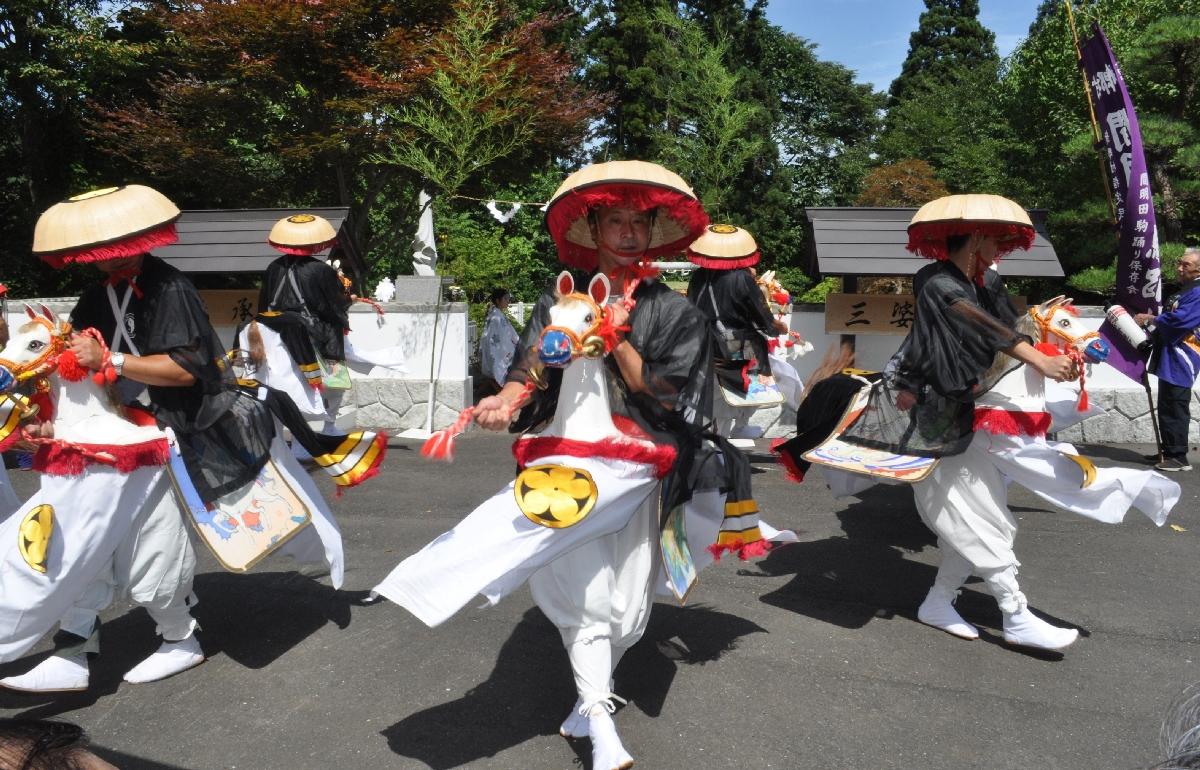 三婆羅塚の前で間明田駒踊りを奉納する同踊り保存会のメンバー