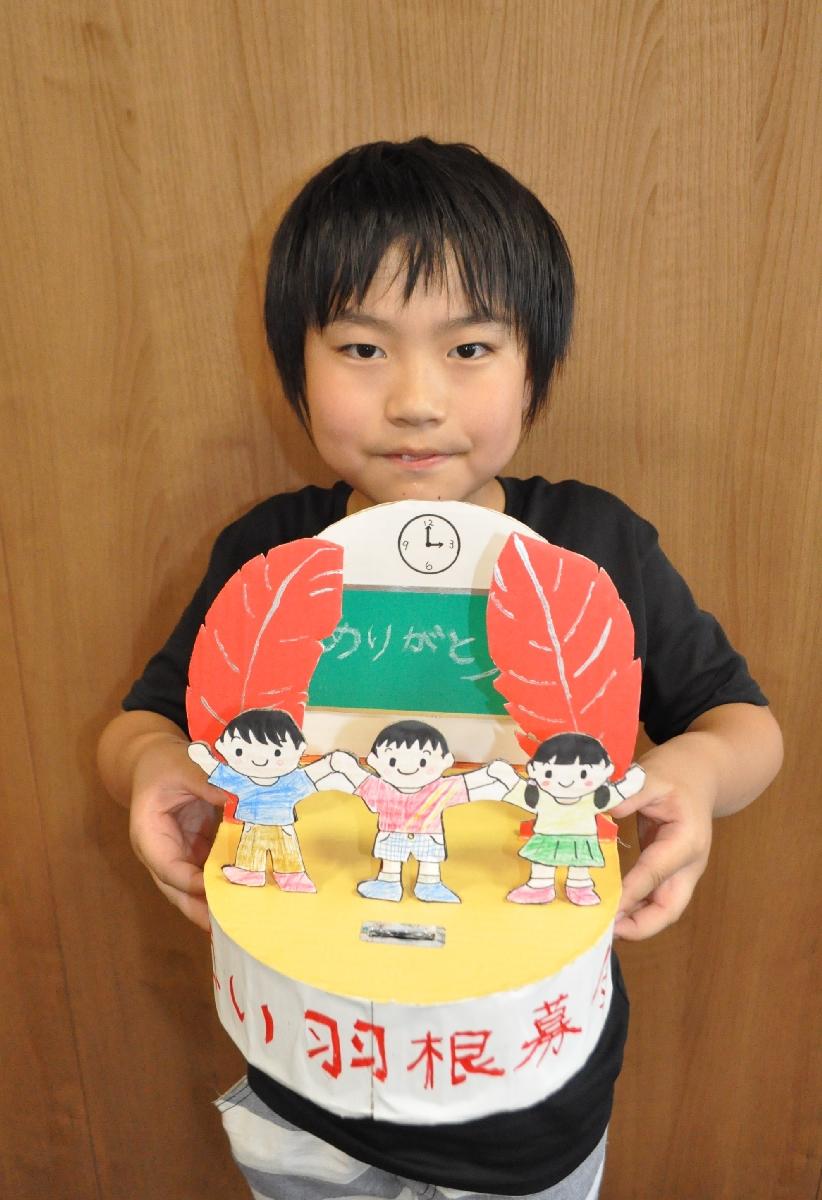最優秀賞を獲得した募金箱を掲げる名久井陽輝君