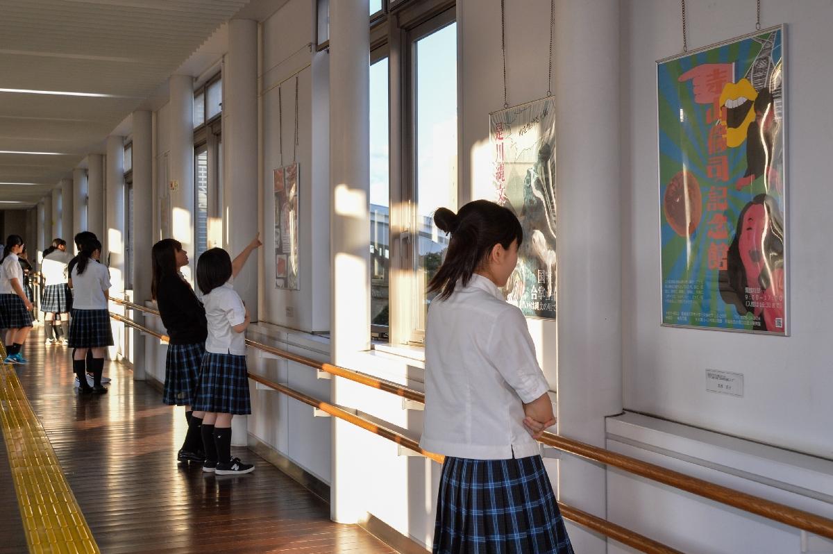 展示されたポスターを眺める工大二高美術コースの生徒