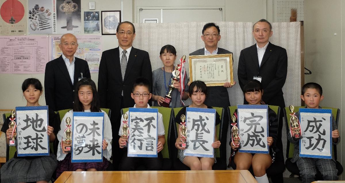 伊藤博章教育長(後列左から2人目)に優勝を報告した児童ら