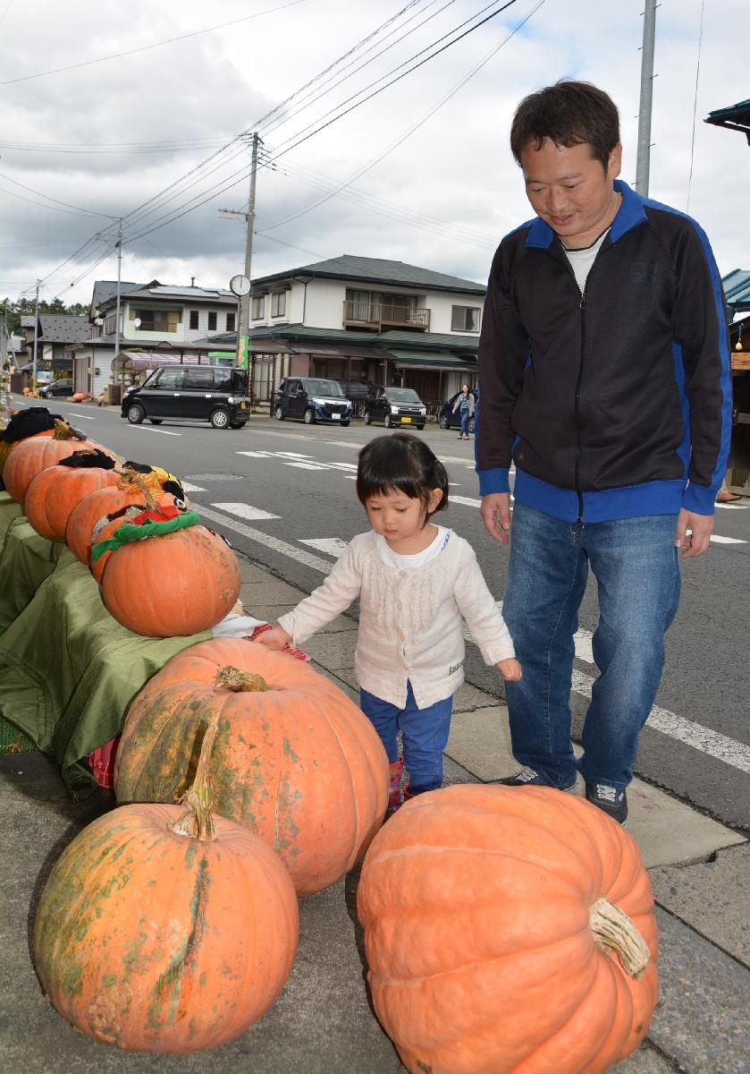 九戸村戸田地区の国道340号沿いに飾られたカボチャを見る家族連れ