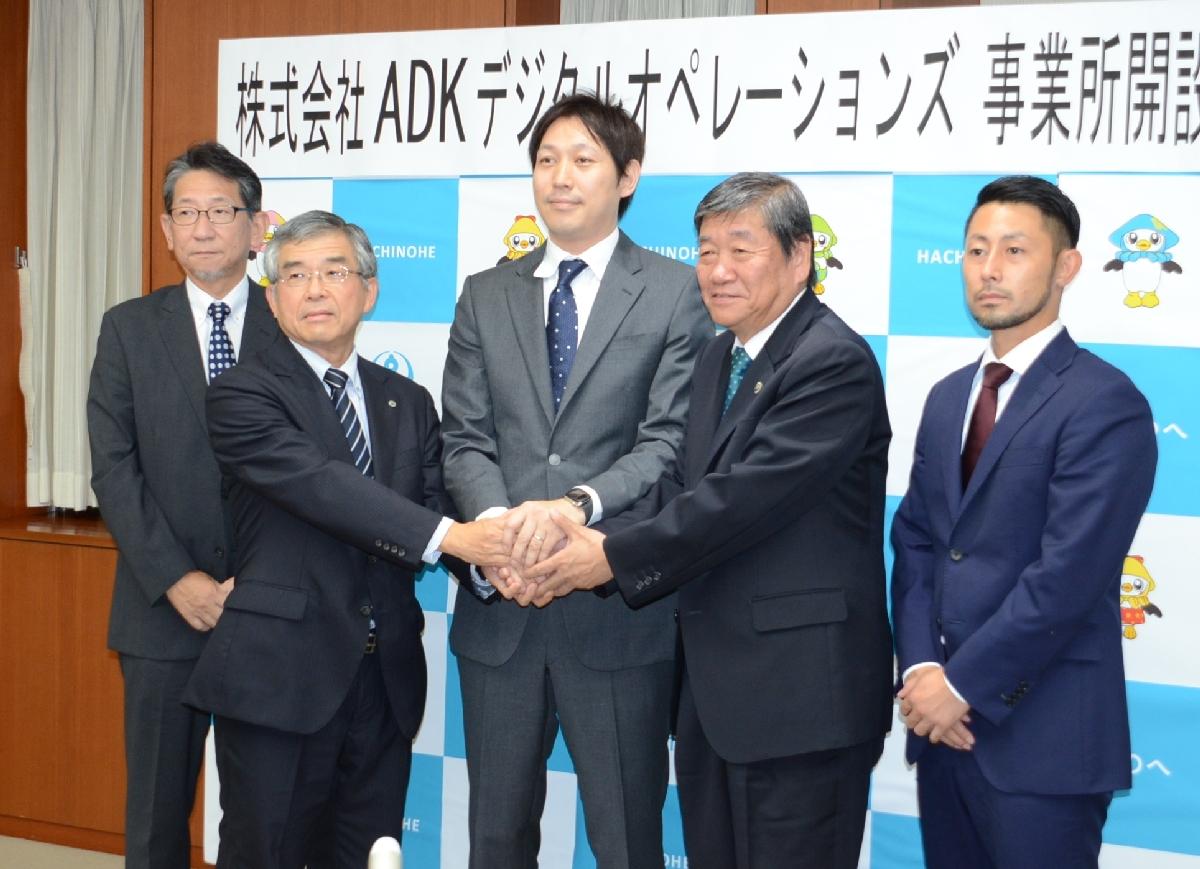 小林眞市長(右から2人目)や田中泰宏部長(左から2人目)と握手する掛谷章往社長(中央)=8日、八戸市庁