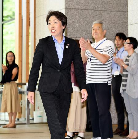 職員らの出迎えを受けて初登庁する橋本五輪相=12日午前、内閣府