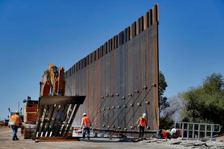 米西部アリゾナ州ユマでメキシコ国境沿いにフェンスを設置する業者=10日(AP=共同)