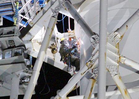福島第1原発1、2号機の共用排気筒の解体作業で、電動のこぎりで排気筒を切断する作業員(中央)=3日午後、福島県大熊町(東京電力提供)