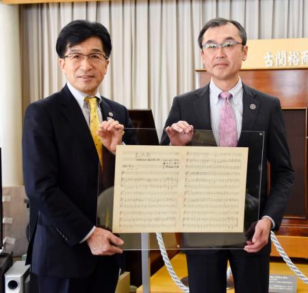 JICAの担当者から、古関裕而さんが作曲した青年海外協力隊の隊歌の楽譜を受け取る福島市の木幡浩市長(左)=9日、福島市