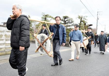 大きな鏡餅を寺まで運ぶ男性ら=9日、鳥取県境港市