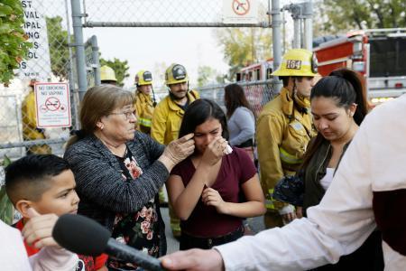 14日、米ロサンゼルス近くで、航空燃料が降り注いだ小学校から避難した児童ら(AP=共同)