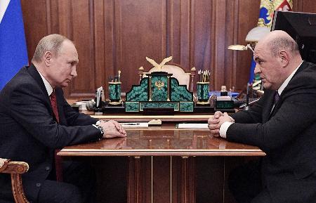 15日、モスクワのクレムリンで会談するロシアのプーチン大統領(左)とミシュスチン連邦税務局長官(ロシア大統領府提供・タス=共同)