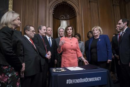 15日、米ワシントンで、上院に提出する弾劾訴追決議に署名するペロシ下院議長(中央)ら(UPI=共同)