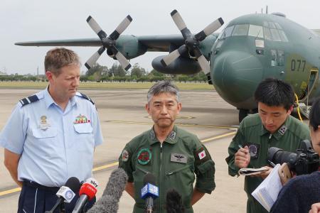 航空自衛隊のC130輸送機(奥)でオーストラリア東部リッチモンドに到着し、取材に応じる太田将史1等空佐(中央)=16日(共同)