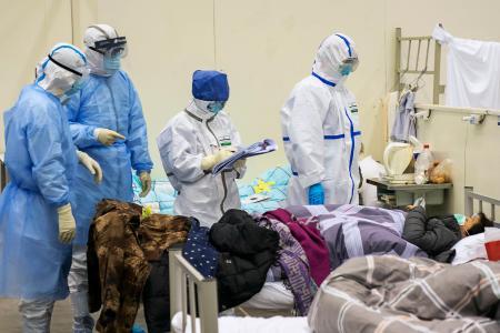 中国・武漢市内のホールに臨時に設置された病院で、新型肺炎患者に対応する医療従事者ら=10日(新華社=共同)
