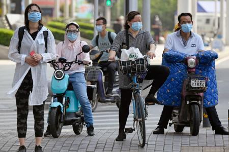 中国・武漢市内でマスクやゴーグルをした市民=23日(共同)