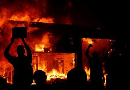 30日、米ミネソタ州ミネアポリスで、燃える建物の前で手を上げるデモ参加者(ロイター=共同)