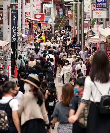 緊急事態宣言が解除されて初の日曜日を迎えた東京・原宿の竹下通りをマスクをして歩く人たち=31日午後