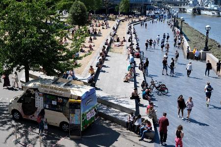 暑さもあり、ロンドン市内のテムズ川の河畔に繰り出した多くの人たち=5月31日(ロイター=共同)