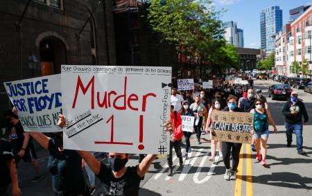 5月31日、米ボストンでプラカードを掲げて抗議する人たち(ロイター=共同)
