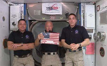 国際宇宙ステーションで記念の星条旗を示すダグラス・ハーリー飛行士(中央)。宇宙船に同乗したロバート・ベンケン飛行士(左)や先に滞在中の飛行士と共に地上と交信した=1日(NASAテレビ)