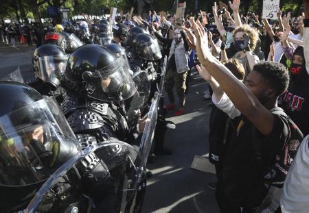 1日、米ワシントンのホワイトハウス近くで、デモ参加者らとにらみ合う治安部隊(UPI=共同)