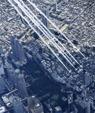 東京都庁(左)上空を飛行する航空自衛隊のブルーインパルス=5月29日、東京都新宿区(共同通信社ヘリから)