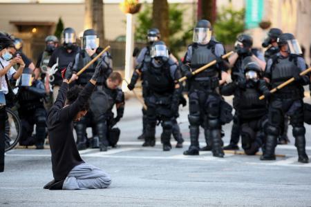 1日、米ジョージア州で、ひざまずいて黒人暴行死事件に抗議する男性(ロイター=共同)