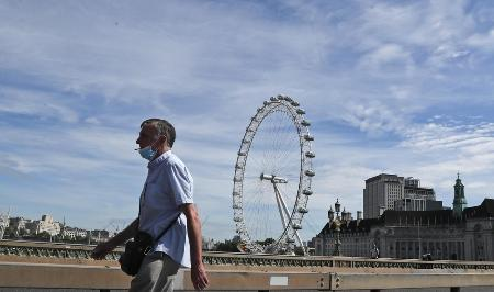 ロンドン市内を歩くマスク姿の男性=5月26日(AP=共同)