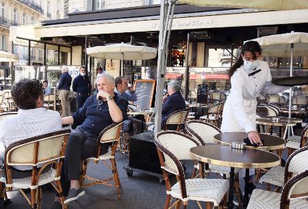 屋外のみの営業を再開したカフェ・レストラン「レリゼサントノレ」を訪れた人たち=2日、パリ(共同)