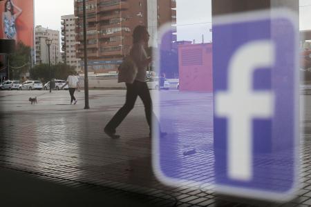 店舗のウインドーに映るフェイスブックのロゴ=2018年、スペイン・マラガ(ロイター=共同)