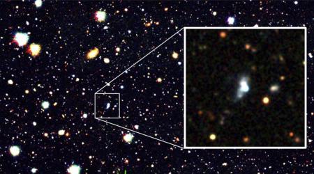 新たに発見された、誕生して1千万年ほどしかたっていないとみられる銀河(拡大部分中央の白い天体)(国立天文台など提供)