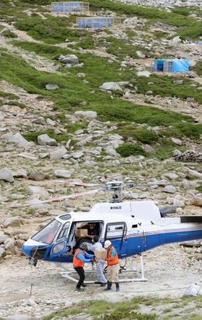 ヘリコプターで乗鞍岳から運ばれてきたライチョウが入った段ボール箱を運ぶ関係者=1日午前、長野県の中央アルプス駒ケ岳(代表撮影)
