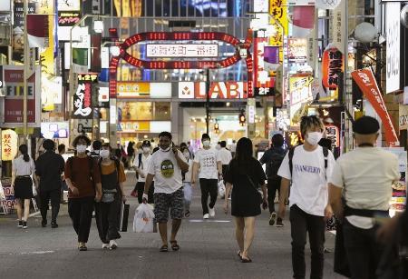 東京・新宿の歌舞伎町をマスク姿で行き交う人たち=7月21日夜