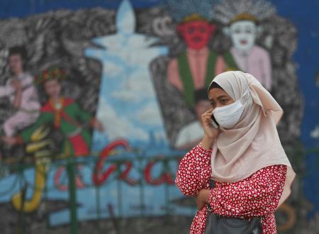 マスク姿で電話をする女性=7月20日、インドネシア・ジャカルタ(AP=共同)