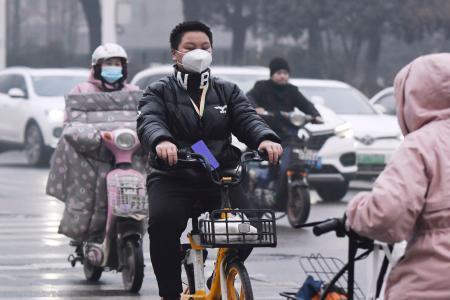 朝の通勤時間帯、マスク姿で自転車に乗る市民=23日、中国・武漢(共同)