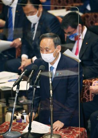 衆院予算委で答弁する菅首相。新型コロナ感染対策のためアクリル板が演台の前に置かれた=25日午前